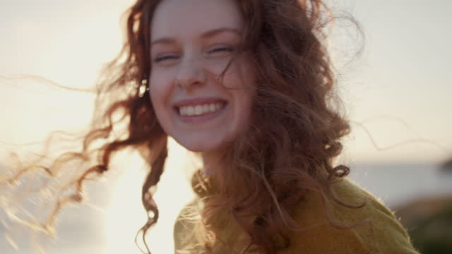 woman with red curly hair in wind at sunset - endurance stock videos & royalty-free footage