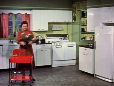 1957 woman with red dress lifting pot of flowers from small table in kitchen / industrial - red dress stock videos & royalty-free footage