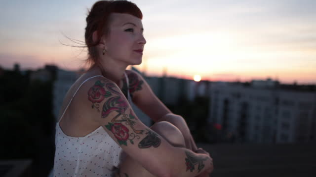 stockvideo's en b-roll-footage met woman with red hair and tattoos enjoying sunset on roof top in berlin, germany - tatoeage