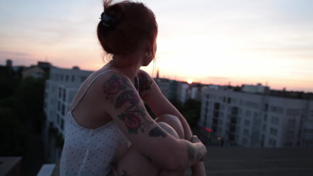 vídeos de stock, filmes e b-roll de woman with red hair and tattoos enjoying sunset on roof top in berlin, germany - telhado