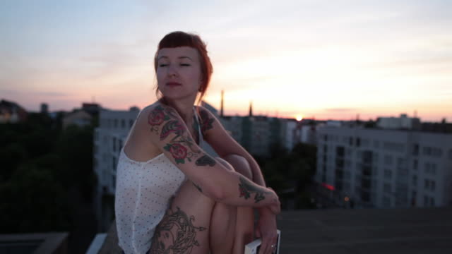 Woman with red hair and tattoos enjoying sunset on roof top in Berlin, Germany