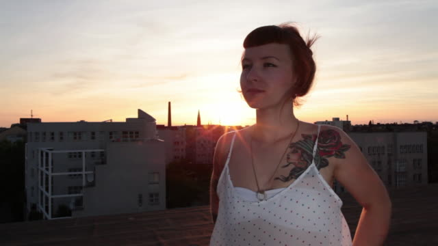 woman with red hair and tattoos looking out over urban berlin from roof top at sunset - dach stock-videos und b-roll-filmmaterial