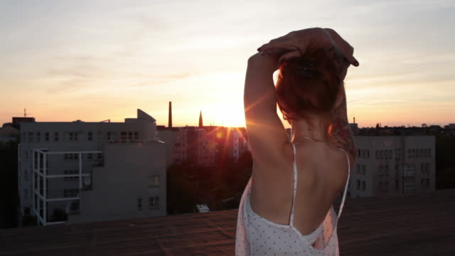 Woman with red hair and tattoos looking out over urban Berlin from roof top at sunset
