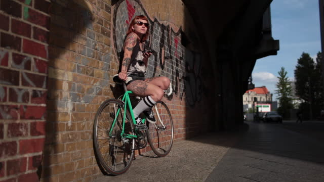 Woman with red hair and tattoos sitting on bike looking at mobile device in the sunshine.