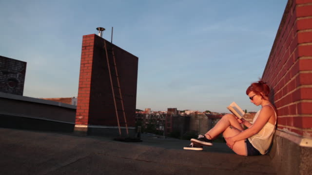 woman with red hair and tattoos sitting on roof top in berlin at sunset reading - gambe accavallate video stock e b–roll