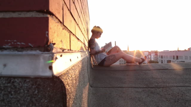 Woman with red hair and tattoos sitting on roof top in Berlin at sunset reading
