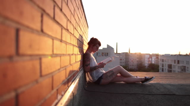 vídeos de stock, filmes e b-roll de woman with red hair and tattoos sitting on roof top in berlin at sunset reading - lendo