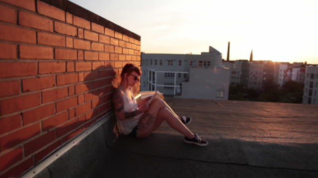 woman with red hair and tattoos sitting on roof top in berlin at sunset reading - wand stock-videos und b-roll-filmmaterial