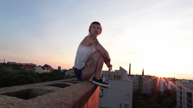 woman with red hair and tattoos sitting on roof top in berlin at sunset smoking - smoking issues stock videos & royalty-free footage