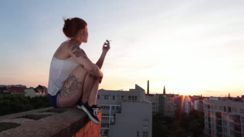vídeos de stock, filmes e b-roll de woman with red hair and tattoos sitting on roof top in berlin at sunset smoking - charuto