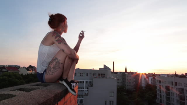 woman with red hair and tattoos sitting on roof top in berlin at sunset smoking - sigaretta video stock e b–roll