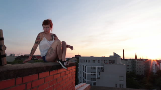 Woman with red hair and tattoos sitting on roof top in Berlin at sunset smoking
