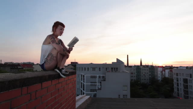 vídeos y material grabado en eventos de stock de woman with red hair and tattoos sitting on roof top in berlin at sunset reading - sentado