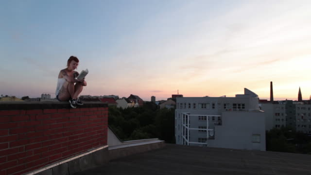 woman with red hair and tattoos sitting on roof top in berlin at sunset reading - legs crossed at ankle stock videos and b-roll footage