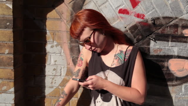 Woman with red hair and tattoos standing in sunshine looking at mobile phone.