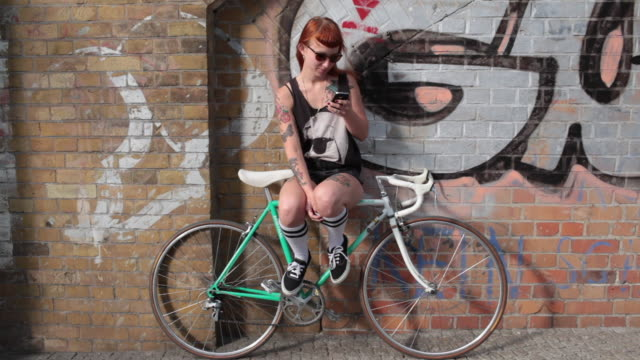 Woman with red hair sitting on bike leaning against graffiti wall, texting.