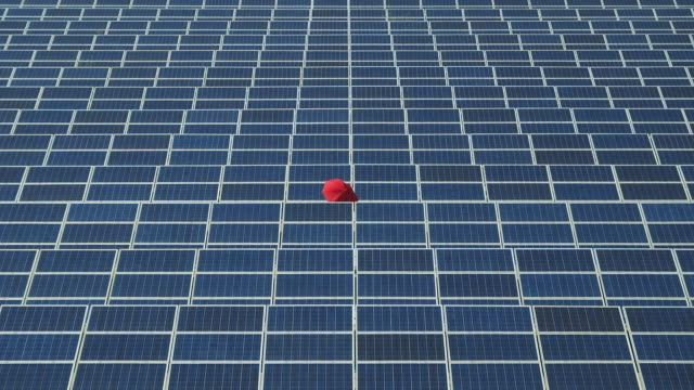 WS Woman with red umbrella standing in photovoltaic (solar) plant / Malaga, Spain