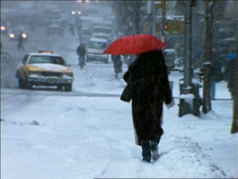 Woman with red umbrella walking on city street in blizzard / NYC