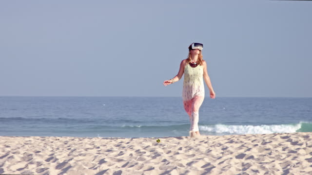 woman with reddish brown hair - using VR glasses outside on a beach - shot-1: medium / appearing from behind the hill until the top of the sand dune -