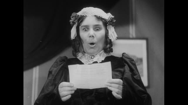 ms woman with ringlet curls and bows in her hair reading a telegram and opening her mouth in surprise / united kingdom - telegram stock videos and b-roll footage