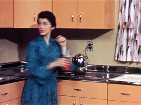1957 woman with robe standing in kitchen plugging in coffee pot + talking to someone off screen / ind. - plugging in stock videos & royalty-free footage
