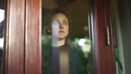 Woman with sad face looks out of window from inside home