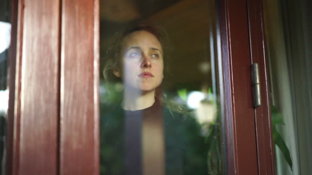 woman with sad face looks out of window from inside home - social issues stock videos & royalty-free footage