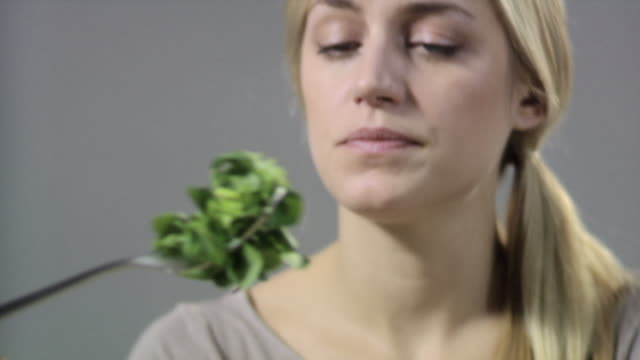 Woman with salad leaves on fork