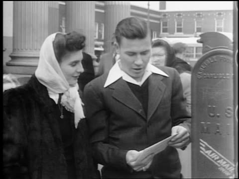 vidéos et rushes de b/w 1944 woman with scarf + man stand by mailbox + look at letter / man puts it in box / lexington, nc - post it