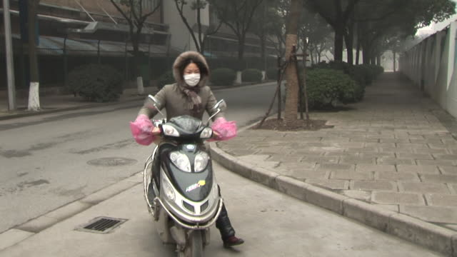 ms, ts, woman with scooter entering shanghai pudong international airport, shanghai, china - 保護マスク点の映像素材/bロール