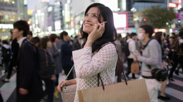 stockvideo's en b-roll-footage met ms a woman with shopping bags talks on her phone / tokyo, japan - shibuya shibuya station