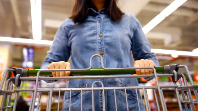 woman with shopping cart in supermarket - merchandise stock videos & royalty-free footage