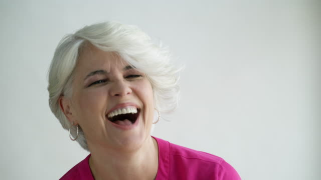 Woman with short hair laughing and nodding, studio shot.