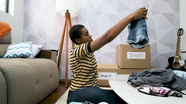 vídeos y material grabado en eventos de stock de mujer con pelo corto seleccionando ropa para la donación en la sala de estar. - sólo mujeres jóvenes