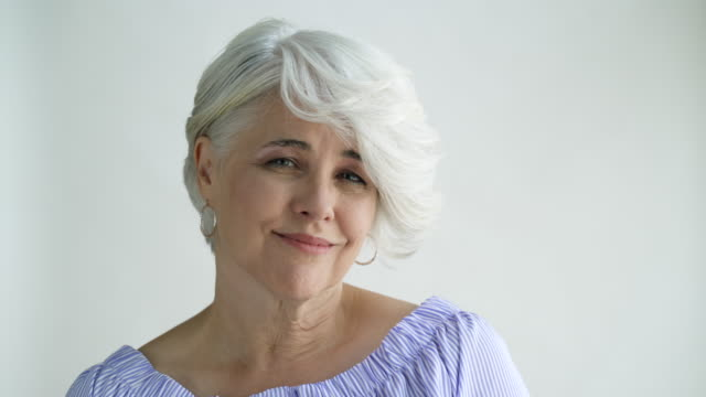Woman with short hair shaking and nodding her head, studio shot.