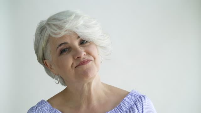 Woman with short hair shaking her head no, studio shot.