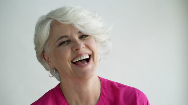 Woman with short hair smiling and laughing, studio shot.