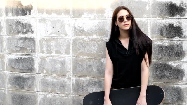 vidéos et rushes de femme avec planche à roulettes - lunette soleil