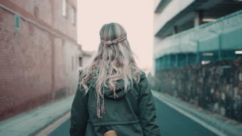 vídeos y material grabado en eventos de stock de mujer caminando por la calle con monopatín - young women