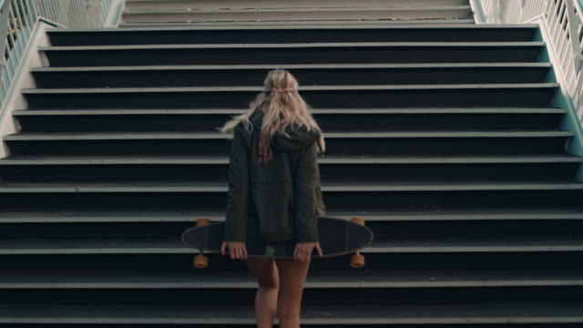 stockvideo's en b-roll-footage met woman with skateboard walking on street - trappen