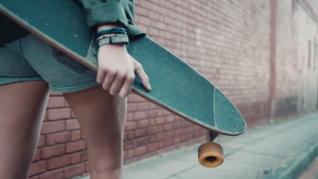 vídeos y material grabado en eventos de stock de mujer caminando por la calle con monopatín - surf en longobard