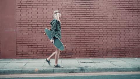 vídeos y material grabado en eventos de stock de mujer caminando por la calle con monopatín - hípster urbano