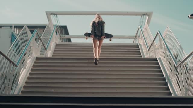 donna con skateboard a piedi sulla strada - scale video stock e b–roll