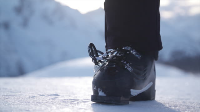 a woman with ski boots preparing to go skiing in the snow at a ski resort. - slow motion - handschuh stock-videos und b-roll-filmmaterial