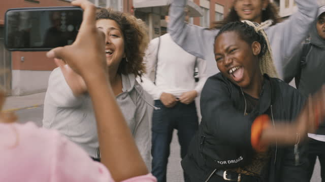 woman with smart phone filming cheerful friends dancing on street in city - mixed race person stock videos & royalty-free footage