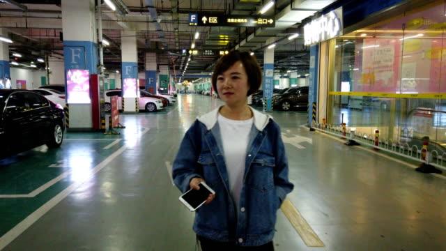 woman with smart phone in parking garage - 立体駐車場点の映像素材/bロール