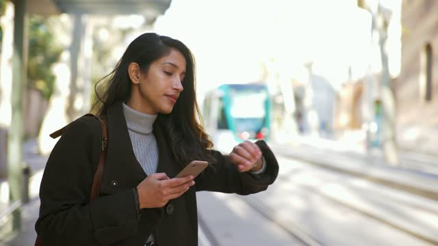 woman with smartphone looking on her watch at tram station - tram stock videos & royalty-free footage