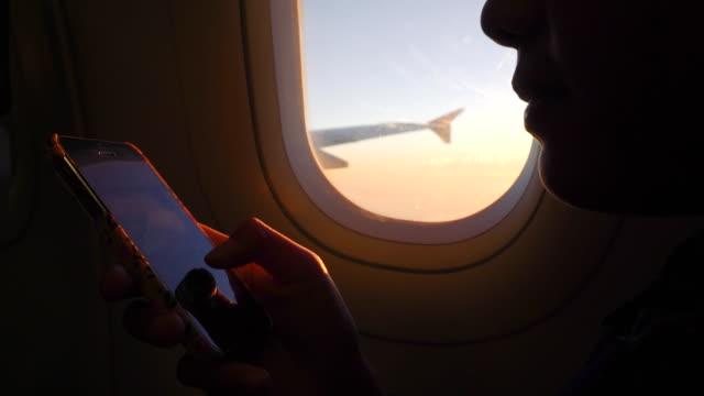 Frau mit Smartphone auf Flugzeug ein Sonnenuntergang