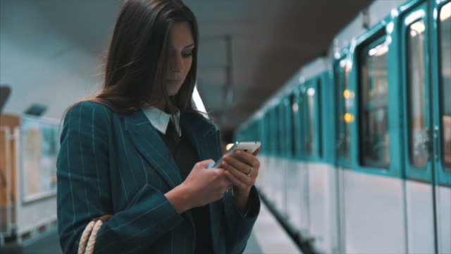 vídeos de stock e filmes b-roll de woman with smartphone travelling by subway - a caminho