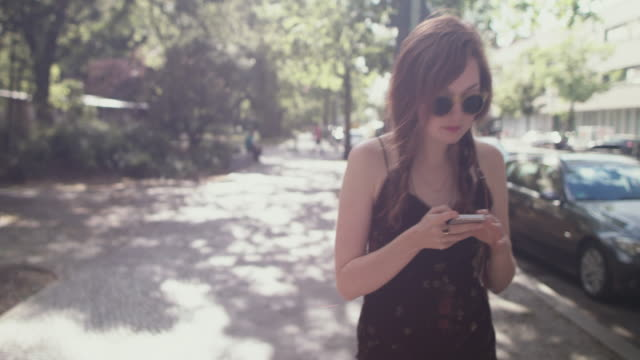 stockvideo's en b-roll-footage met woman with smartphone - blijf staan